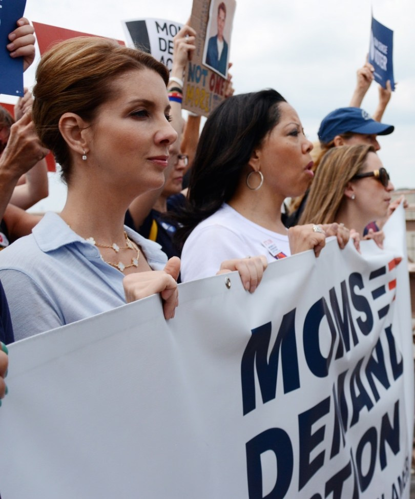 Shannon Watts of Moms Demand standing in protest line holding banner with others